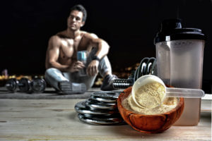 Image of an athlete with whey protein powder and and weights illustrating some benefits of supplements when exercising.