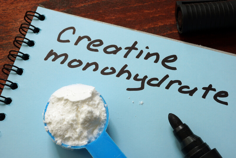 Creatine monohydrate and scoop with white powder.