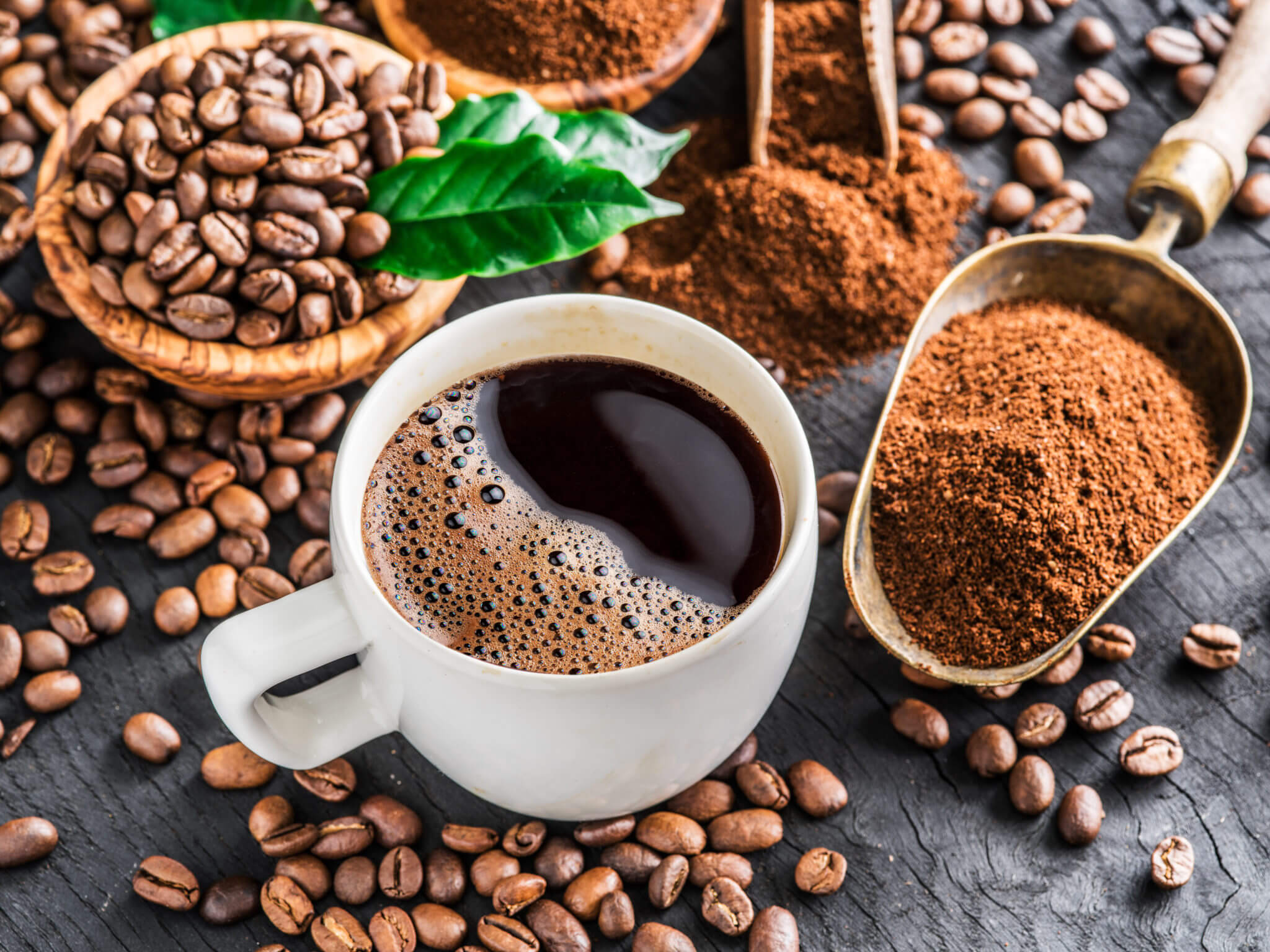 Caffeine from roasted coffee beans, ground coffee and cup of coffee on wooden
