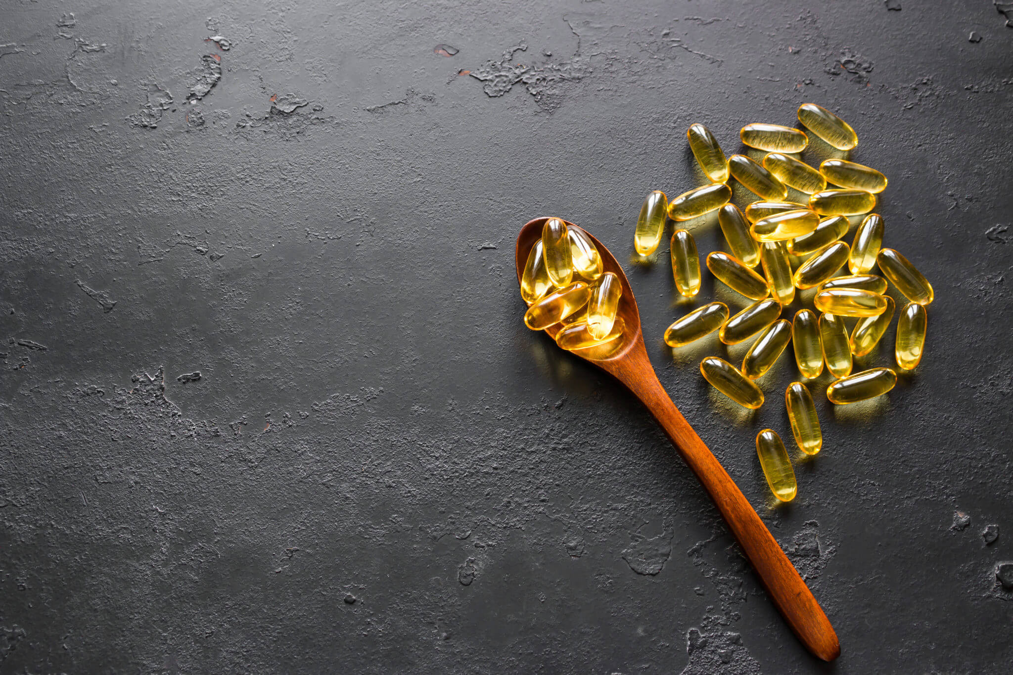 Wooden Spoon And Fish Oil Capsules On A Black Background With Sp