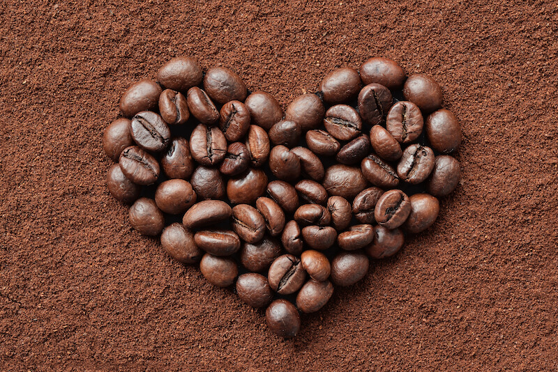 Decaf Coffee beans heart on coffee powder background - Is Decaf Coffee Good for You?