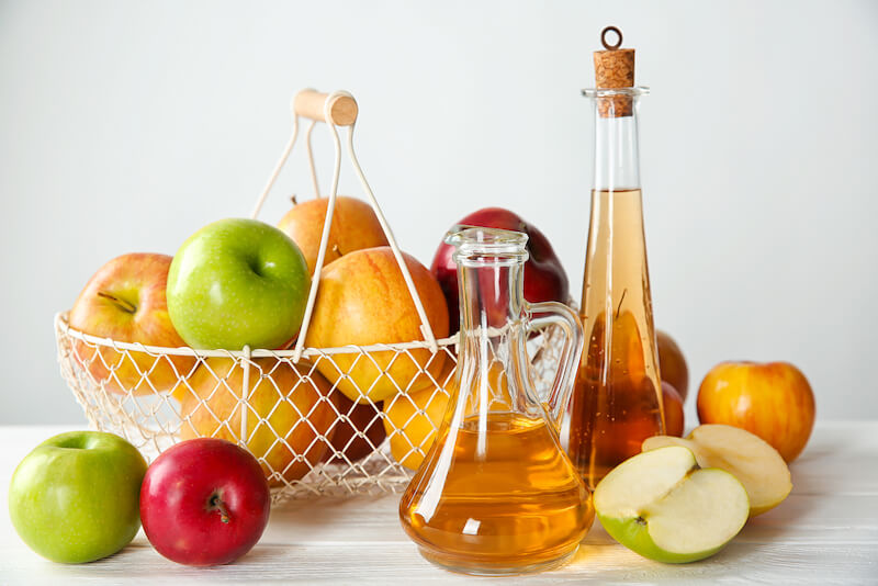 Glass bottle, jug with apple vinegar and basket full of fresh fruit on table